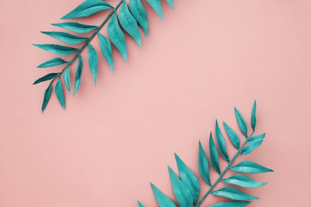 Hermoso borde azul deja sobre fondo rosa Foto gratis