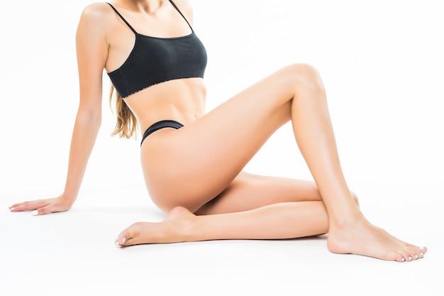Hermoso cuerpo femenino aislado sobre la pared blanca. sentada en el suelo toca la pierna con la mano, el concepto de belleza y cuidado de la piel. Foto gratis