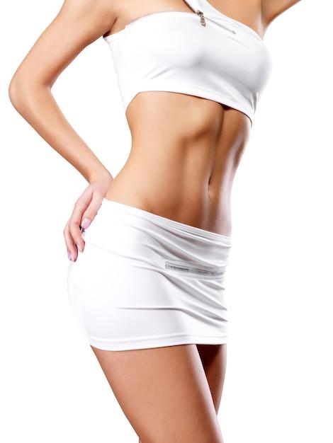 Hermoso cuerpo femenino sano en ropa deportiva blanca Foto gratis