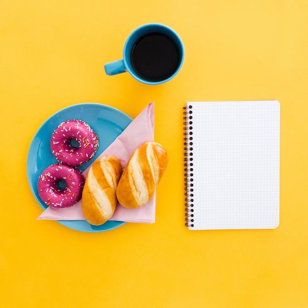 Hermoso desayuno con donas y taza de café con cuaderno en amarillo Foto gratis