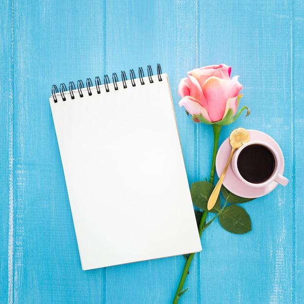 Hermoso desayuno con rosas y una taza de café en madera azul Foto gratis
