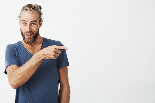 Hermoso hombre fuerte con peinado atractivo y barba en camisa azul apuntando a un lado con expresión de sorpresa Foto gratis