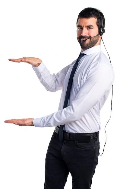 Hermoso hombre de telemercadeo sosteniendo algo Foto gratis