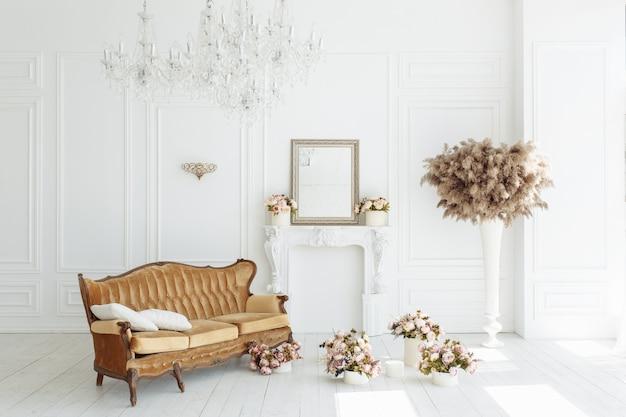 Hermoso interior blanco clásico con una chimenea, un sofá marrón y una lámpara de araña vintage. Foto gratis
