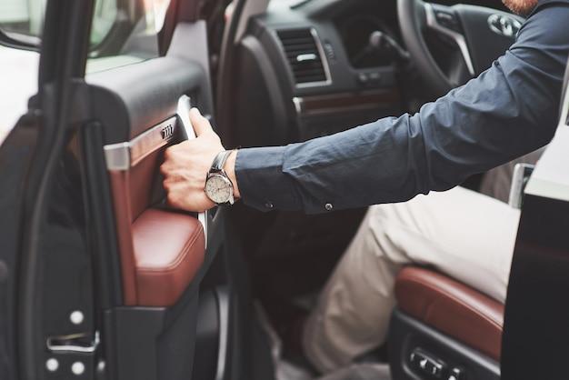 Hermoso joven en traje completo mientras conduce un automóvil. Foto gratis
