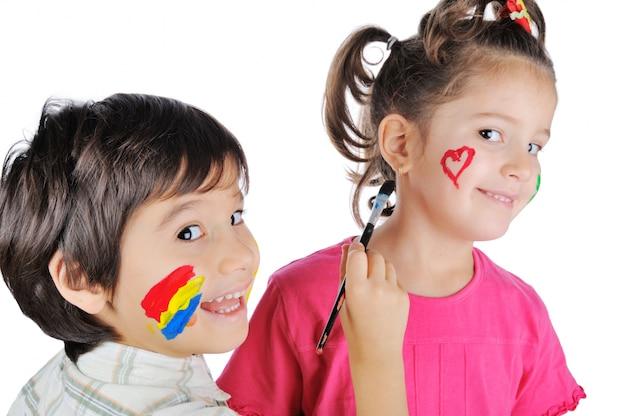 Hermoso niño pintando la cara de su hermana | Foto Premium