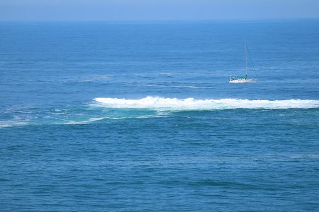 Hermoso océano azul con las olas rompientes y un yate blanco Foto Premium