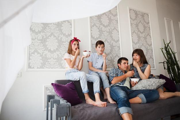 Hermoso padre y sus hijos comiendo fresas mientras están sentados en un sofá Foto gratis