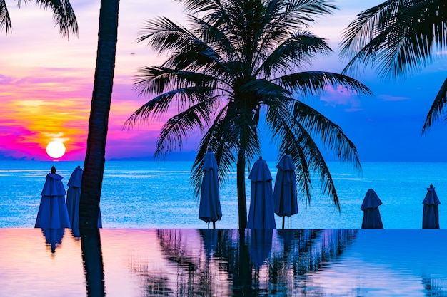 Hermoso paisaje de naturaleza al aire libre con mar oceánico y palmera de coco alrededor de la piscina en sunrsie o atardecer Foto gratis