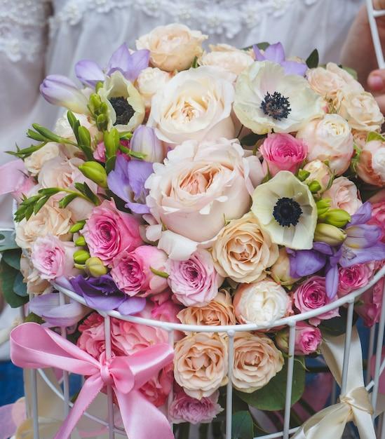 Un hermoso ramo de flores de color pastel en un contenedor de jaula Foto gratis