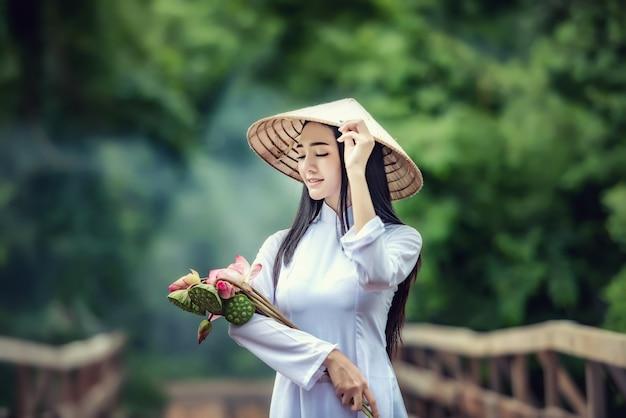 Hermoso retrato de chicas asiáticas con ao-dai vietnam traje tradicional mujer, caminar el puente con lotus, en vietnam. Foto Premium