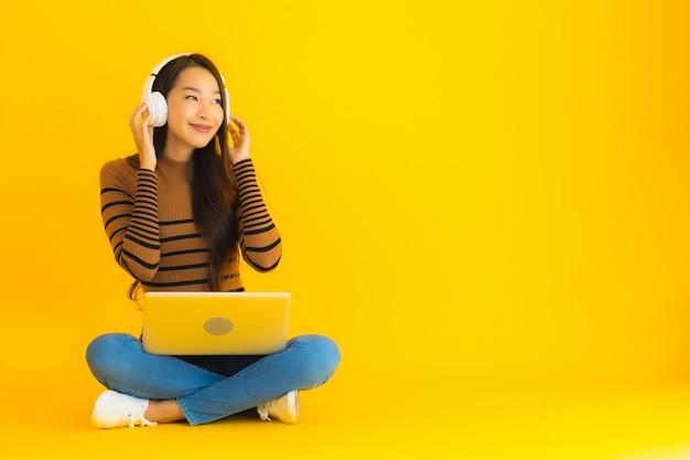 Hermoso retrato joven mujer asiática sentarse en el suelo con el portátil y los auriculares en la pared amarilla Foto gratis