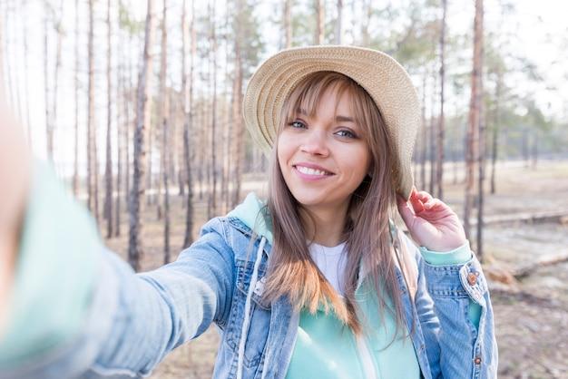 Hermoso retrato de un viajero femenino que toma autorretrato en el bosque Foto gratis
