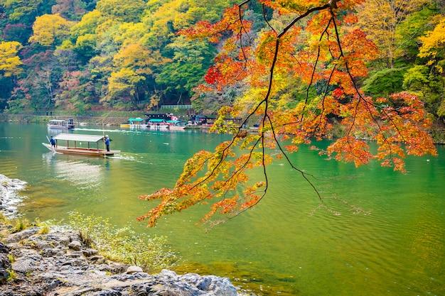 Hermoso río arashiyama con árbol de hoja de arce y bote alrededor del lago Foto gratis