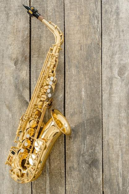 Hermoso saxofón dorado en madera Foto Premium