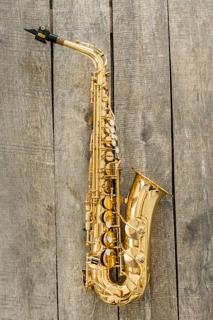 Hermoso saxofón dorado sobre superficie de madera Foto Premium
