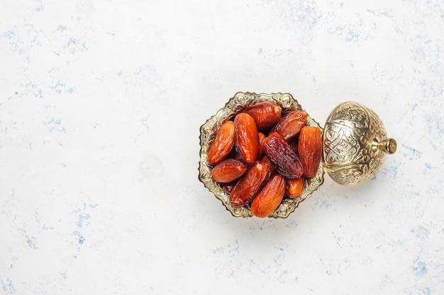 Hermoso tazón lleno de frutas de fecha que simbolizan el ramadán, vista superior Foto gratis