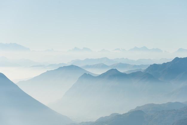 Hermoso tiro de altas colinas blancas y montañas cubiertas de niebla Foto gratis