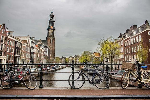 Hermoso tiro de bicicletas se inclinó de nuevo la valla en un puente sobre el río Foto gratis