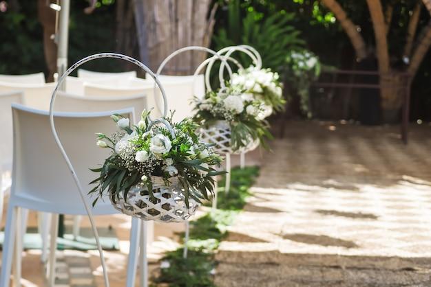 Hermosos arreglos florales de boda a lo largo del pasillo Foto Premium