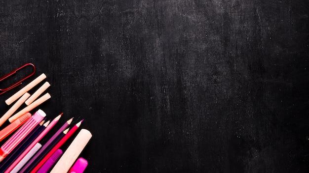 Herramientas de la escuela en el escritorio negro Foto gratis