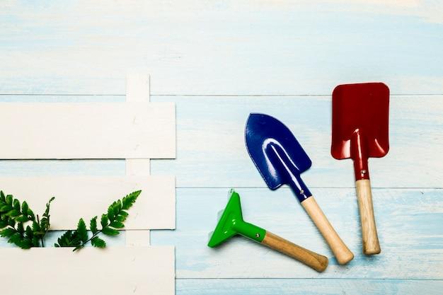 Herramientas de jardín con pieza de valla. Foto gratis