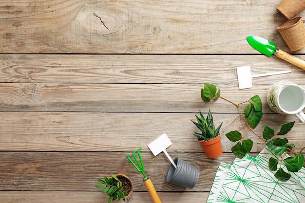 Herramientas de jardinería y flores en maceta sobre fondo de madera vintage Foto Premium