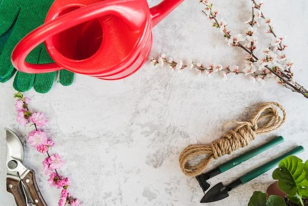 Herramientas de jardinería; regadera; guantes; ramitas de flores; cuerda sobre fondo de hormigón Foto gratis