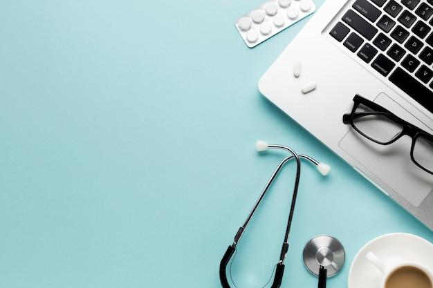 Herramientas médicas con bloc de notas; computadora portátil y una taza de café sobre el escritorio Foto gratis