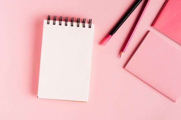 Herramientas de oficina color rosa de superficie. Foto gratis