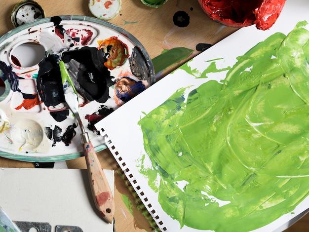 Herramientas de pintura desordenadas junto a pintura verde. Foto gratis