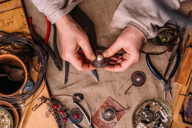 Herramientas de trabajo de alambre de cobre hechas a mano sobre la mesa con accesorios. concepto de arte de personas artesanales Foto Premium