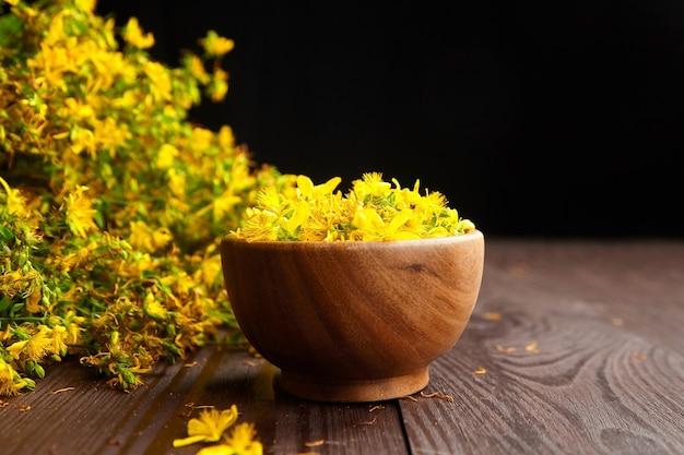 Hierba de san juan (hypericum perforatum) flores amarillas en recipiente de madera Foto Premium