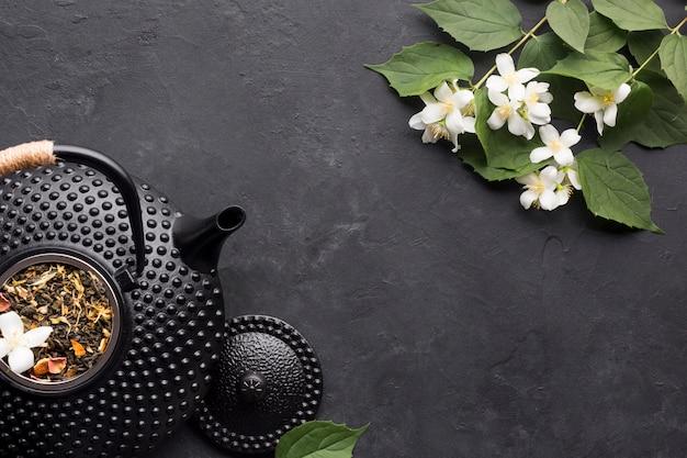 Hierba seca del té con flor de jazmín blanco fresco en negro con textura Foto gratis