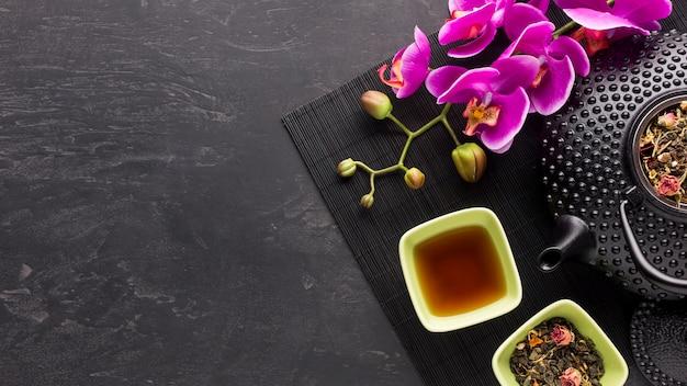Hierba de té seca y flor de orquídea rosada con tetera en superficie negra Foto gratis