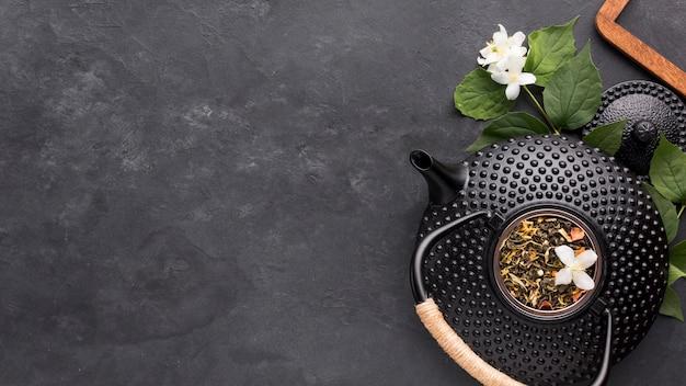 Hierba de té seca con tetera negra y flor de jazmín blanca sobre fondo de piedra pizarra Foto gratis