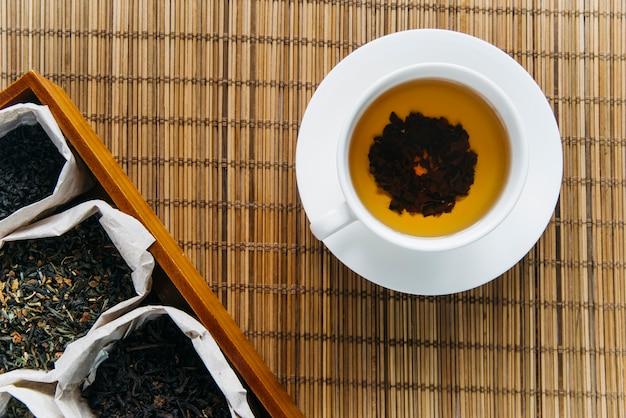 Hierba de té seco con té de hierbas en mantel individual Foto gratis