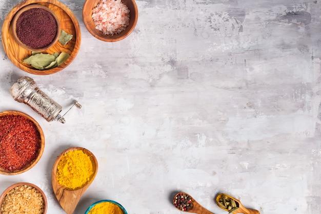 Hierbas secas y alimentos de especias en cucharas y cuencos en piedra como marco, plano Foto Premium