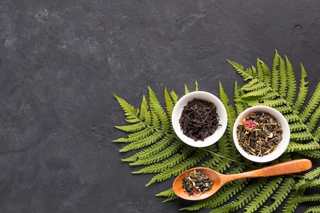 Las hierbas secas del té en el cuenco de cerámica con el helecho se van en fondo negro Foto gratis