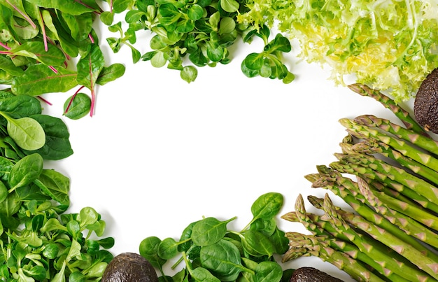 Hierbas verdes, espárragos y aguacate negro sobre un fondo blanco. vista superior. lay flat Foto gratis