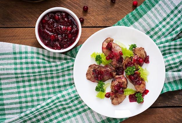 Hígados de pollo con salsa de arándanos y lechuga. vista superior Foto Premium