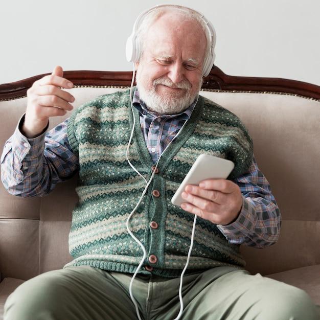 Higha ngle senior en el sofá tocando canciones Foto gratis