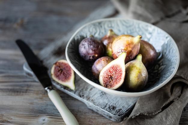 Higos maduros frescos en un recipiente sobre una mesa de madera oscura. Foto Premium