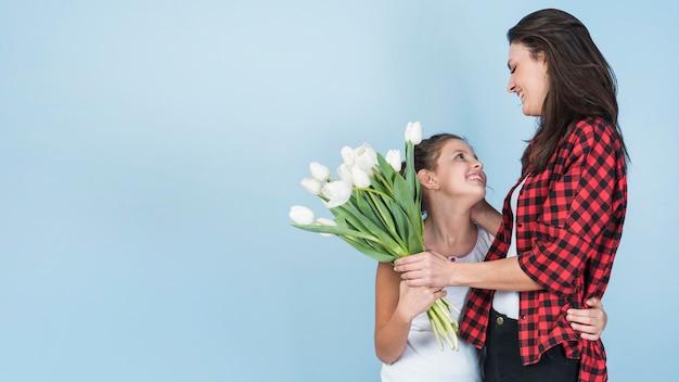 Hija abrazando a la madre y dándole tulipanes blancos Foto gratis