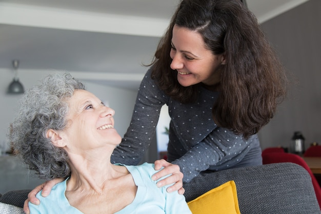 Hija adulta feliz visitando anciana madre Foto gratis