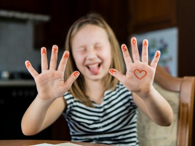 Hija dibujando un corazón en su mano para el día del padre Foto gratis