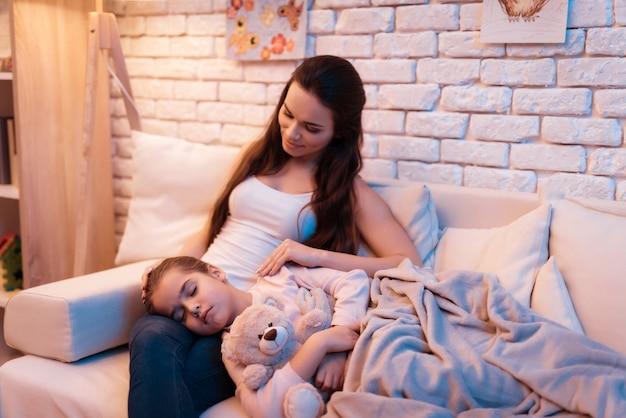 La hija duerme en el regazo de la madre a altas horas de la noche en casa.  | Foto Premium