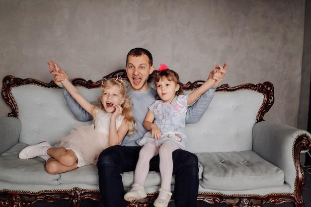 Hija feliz de la familia que abraza a papá y se ríe en día de fiesta Foto gratis