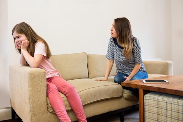 Hija haciendo caso omiso de su madre después de una discusión en la sala de estar Foto gratis