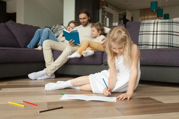 Hija jugando en el piso mientras los padres y su hijo leen un libro Foto gratis